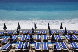 French Riviera beach with blue lounge chairs